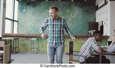 Happy young businessman walking through the modern office and doing crazy dance. Man in cheerful mood greets with colleagues. Male doing victory after success achievement.