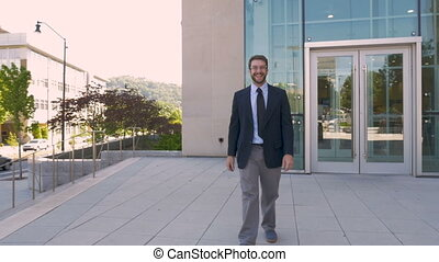 Happy businessman walking towards the camera in slow motion outside - wide