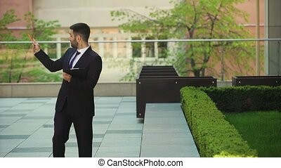 Happy businessman walks down the street with a tablet.