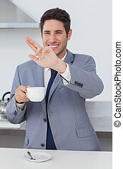 Happy businessman waving at someone in the kitchen
