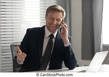 Happy businessman wearing suit laughing talking on phone in office