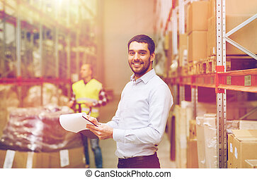 wholesale, logistic, people and export concept - happy businessman or supervisor with clipboards at warehouse