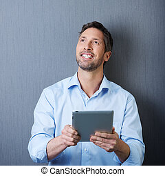 Happy Businessman With Digital Tablet Against Blue Wall