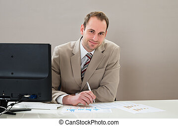 Businessman With Graphs At Desk