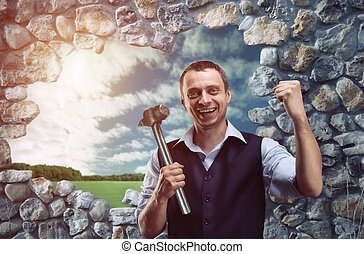 Happy businessman with hammer