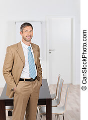 Happy Businessman With Hands In Pockets Standing In Office