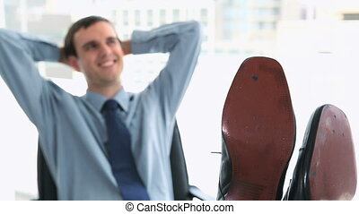 Happy businessman with his feet on a desk