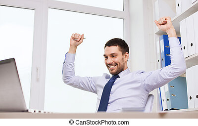 happy businessman with laptop cheering in office