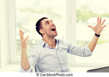 happy businessman with laptop in office