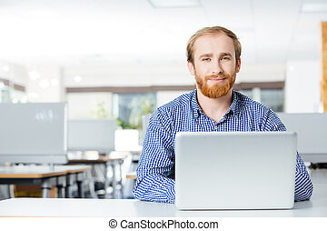 Happy businessman with laptop working on workplace in office