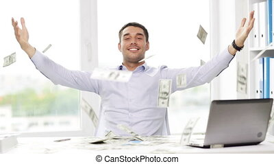 happy businessman with money and laptop in office