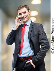 Happy businessman with phone posing in office