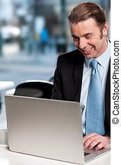 Happy businessman working on laptop