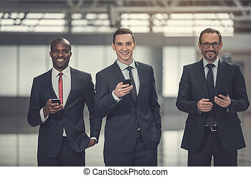 Happy businessmen working with phones