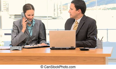 Happy businesspeople after a phone call in an office