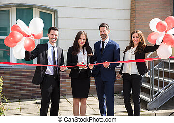 Happy Businesspeople Cutting Ribbon