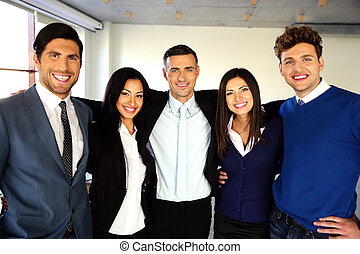 Happy businesspeople standing in office together