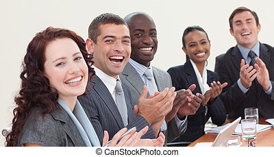 Happy businessteam clapping in a meeting - Happy ...