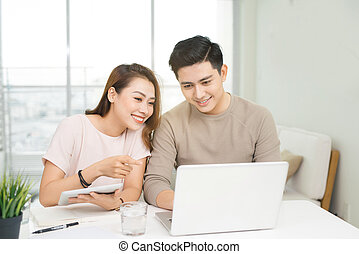 Happy businesswoman and businessman using laptop at workplace in office