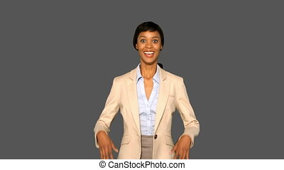 Happy businesswoman cheering on grey background