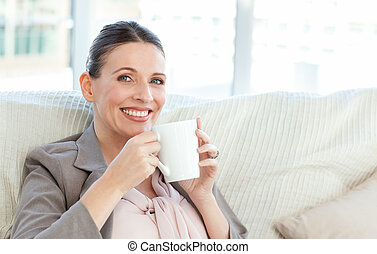 Happy businesswoman drinking a cup of coffee on the sofa