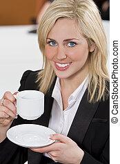 Happy Businesswoman Drinking Coffee In An Office