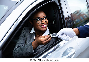 Happy Businesswoman Giving Car Key To Valet - Close-up Of...