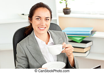 Happy businesswoman holding a cup of coffee sitting in her office at her desk