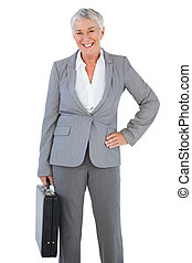 Happy businesswoman holding briefcase and putting her hand on hip on white background