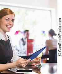 Happy businesswoman holding tablet and wine glass looking at camera in a restaurant