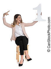 happy businesswoman holds one and looks to side while celebrating
