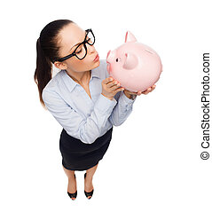 happy businesswoman in eyeglasses with piggy bank -...