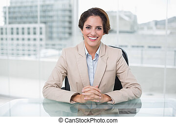 Happy businesswoman looking at camera at her desk