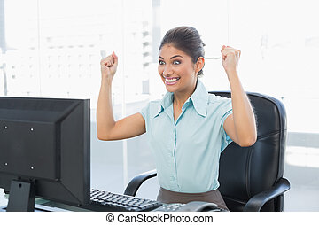 Happy businesswoman looking at computer in office