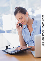 Happy businesswoman looking at her diary and calling