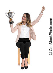 happy businesswoman looks at trophy and celebrates while sitting