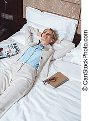 happy businesswoman on bed in hotel