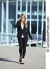 Happy businesswoman on the mobile phone walking on the street