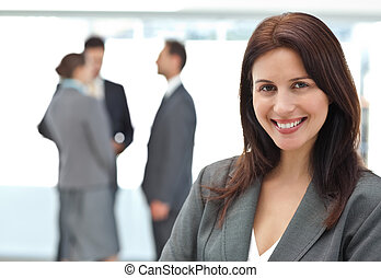 Happy businesswoman posing while her team discussing on the...