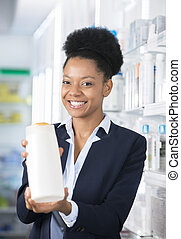 Happy Businesswoman Presenting Bottle In Pharmacy