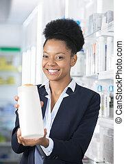 Happy Businesswoman Presenting Bottle In Pharmacy