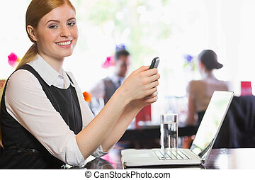Happy businesswoman sending a text looking at camera in a ...