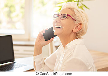 Happy businesswoman sitting at desk in office.