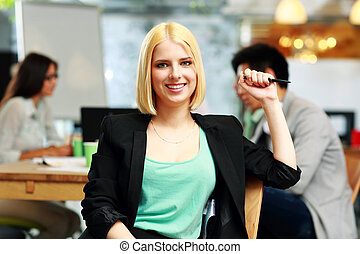 Happy businesswoman sitting in office, with her colleagues in background