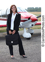 Happy businesswoman standing in front of a plane