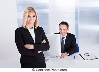 Businesswoman Standing In Front Of Her Colleague Using...