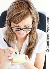 Happy businesswoman taking notes sitting in her office
