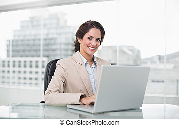 Happy businesswoman typing on laptop at her desk looking at camera in bright office