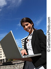 Happy businesswoman using computer outdoors