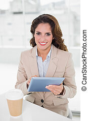 Happy businesswoman using digital tablet at her desk